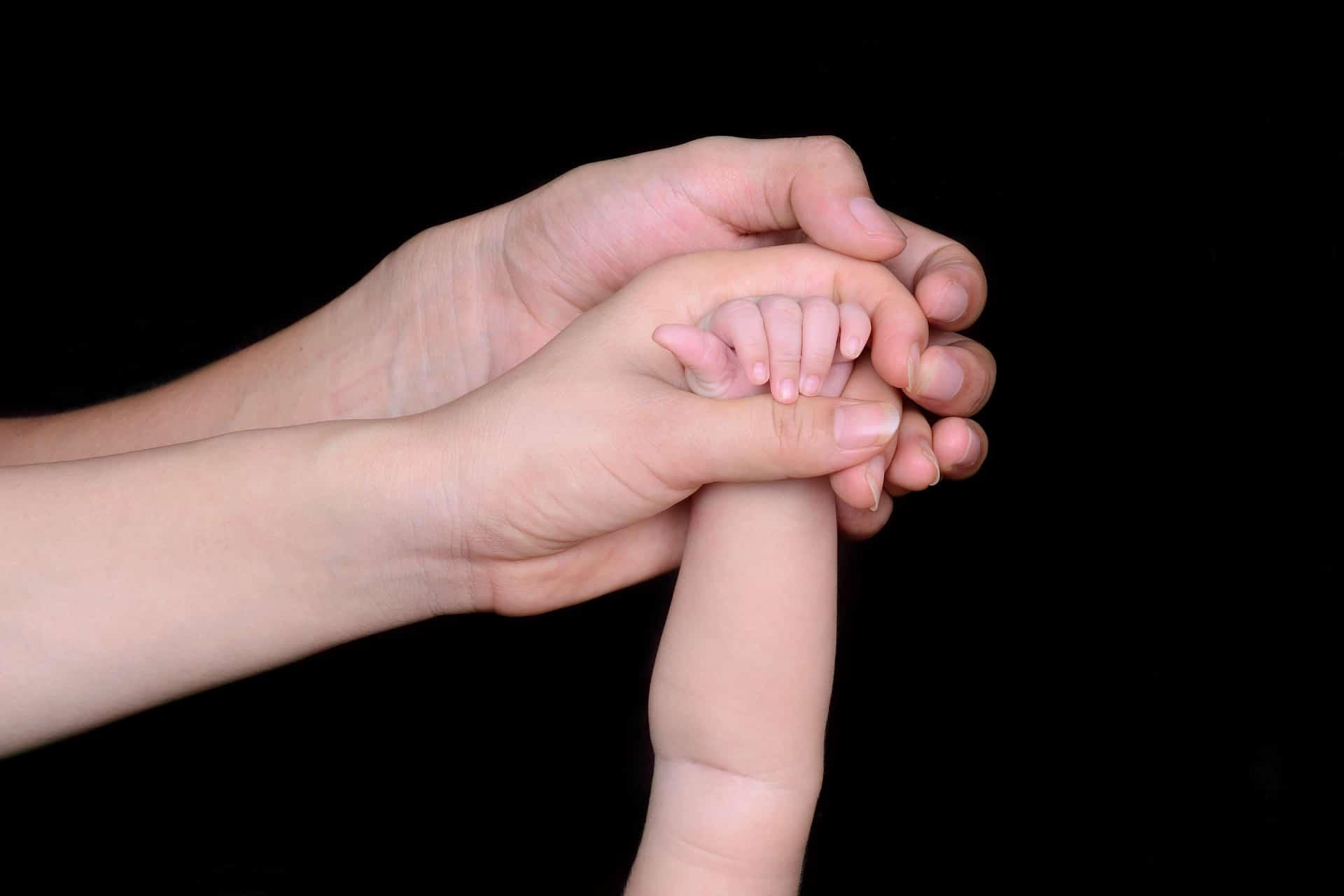 Drei Hände berühren sich, eine Familie mit Baby
