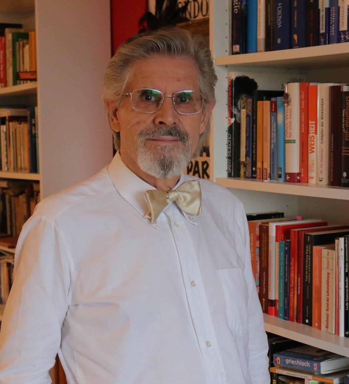 Porträt des Mentaltrainers M. P. Lederer, er steht vor einem Bücherregal
